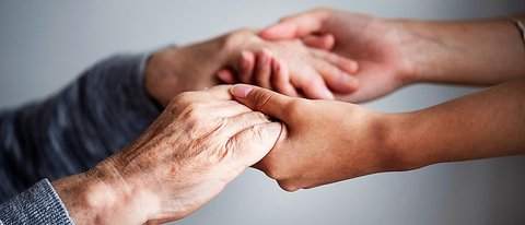 Picture of a younger set of hands on the right holding an elderly pair of hands on the left against a solid gray background