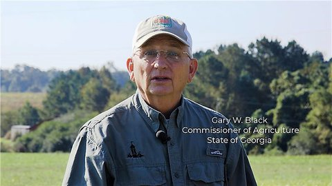 Field with large trees in background Gary Black commissioner of agriculture state of georgia wearing his white and grey baseball cap and a button down long sleeve shirt