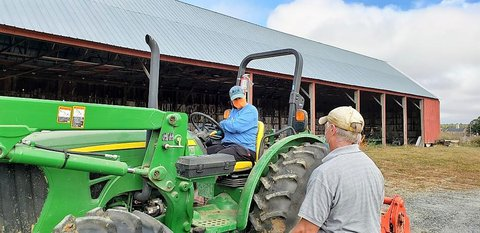 A person in blue sitting on a green tractor talking to a man in gray shirt and tan baseball cap with his back to the camera - there is a large barn or shed in the background
