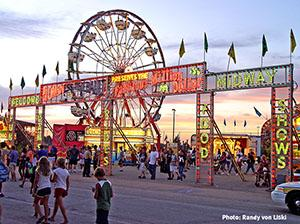 Photo of state fair midway with neon sign and many people walking at twilight. Photo by Randy von Liski.