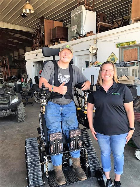 Picture of Kane on the left standing in his tracked stander-wheelchair with Rachel on the right side of the picture next to him inside a large farm implement shed.