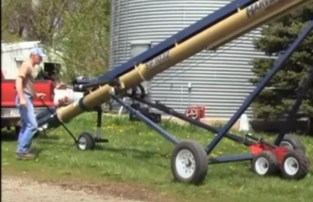 Man walks next to straight grain auger and moves it using the BackSaver 3 Straight Auger Mover. Grain bin and pickup truck are in background.