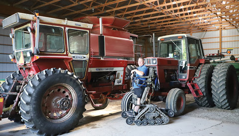 Picture of a large farm shed with a red combine and red tractor in it and in the foreground an AgrAbility client in a standing Trackchair