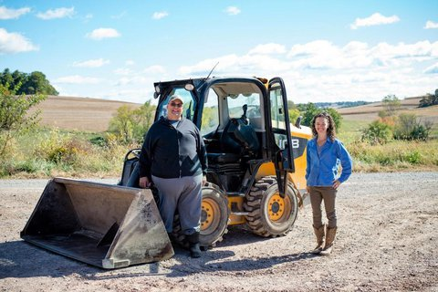Garvin and Abbie in a beautiful quiet hilly area standing by a backhoe on gravel smiling facing the camera
