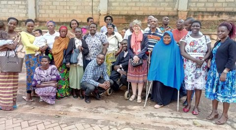 Picture showing a group of African men and women with most of them standing but a few squatting and one in a wheelchair standing on a cement courtyard with a cement block wall behind them.