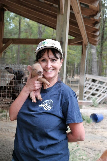 Picture of Paige Tidwell in blue t-shirt and white baseball cap holding a piglet next to her face with her right arm