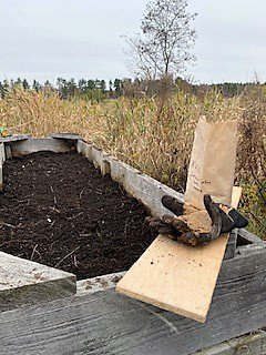 grey wooden planter filled with soil in the middle of a field surrounded by tall grass. There is a plank of wood sitting on the corner of the planter with a pair of gloves and a brown paper bag sitting upon it