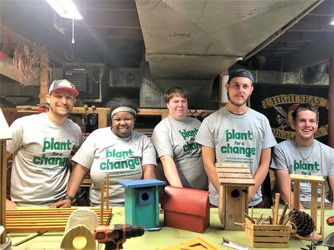 Pic of 5 people standing in a basement shop in front of a table with homemade bird houses and other crafts on it. They are all wearing gray t-shirts that say -  plant for a change.