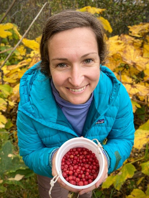 Picture of a woman in a bright blue coat looking up at the camera while standing among yellow fall leaves and holding a white container of red berries.