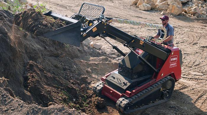 Man operates mini skid steer loader with telescoping bucket as he scoops dirt from high pile.
