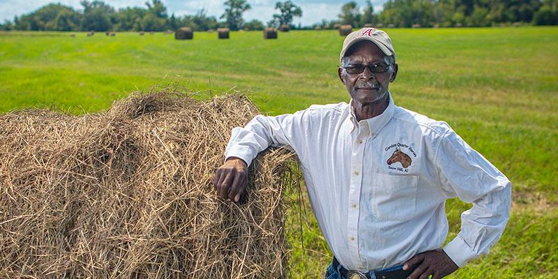 African American farmer stands with right arm on large hay bale with hay field in backgrouns