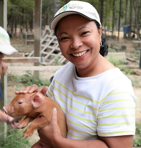 Photo of Jacquline wearing white baseball cap and a white blouse with yellow horizontal stripes - holding a piglet