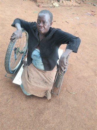 Picture of African woman Agnes sitting on her new BiCrawler on a dirt yard