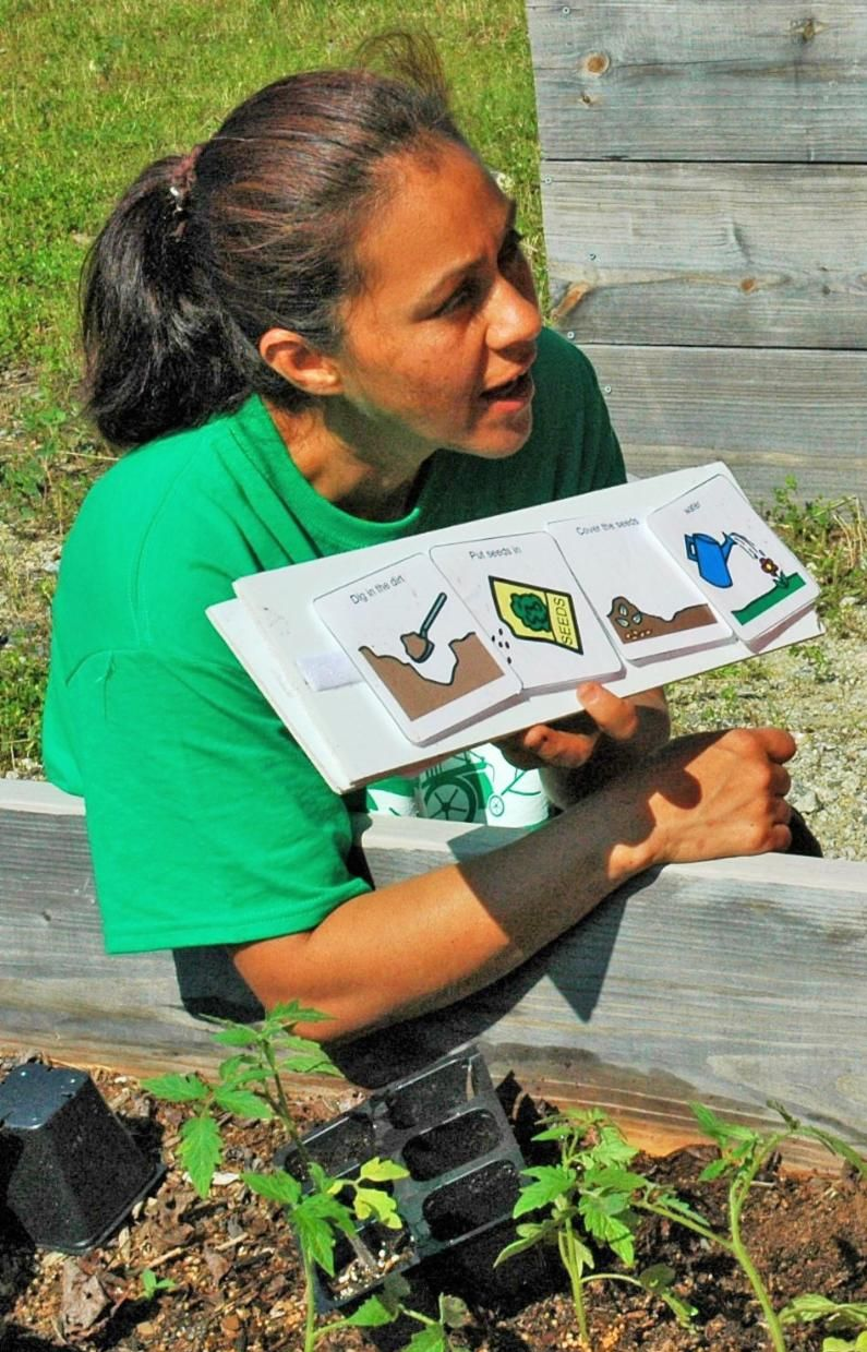 Gardening teacher using pictures to give instructions on gardening tasks such as planting and watering
