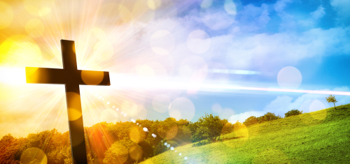 Religious illustration with backlit cross with golden glitter and bokeh and nature landscape background. Horizontal composition