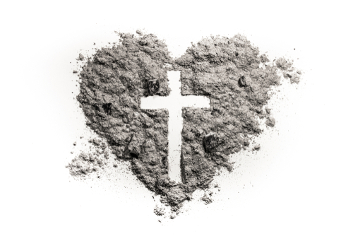 Cross or crucifix in heart symbol made of ash_ sand or dust as Jesus Christ christian passion or chrism_ lent and Ash Wednesday concept