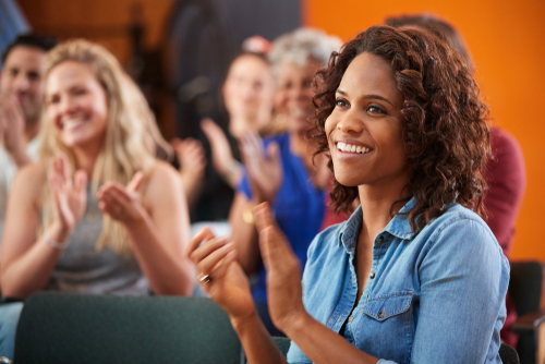 Group Attending Neighborhood Meeting Applauding Speaker In Community Center