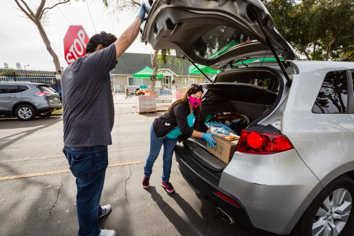 A picture of NHF staff and volunteers loading food boxes into the trunk of a car.