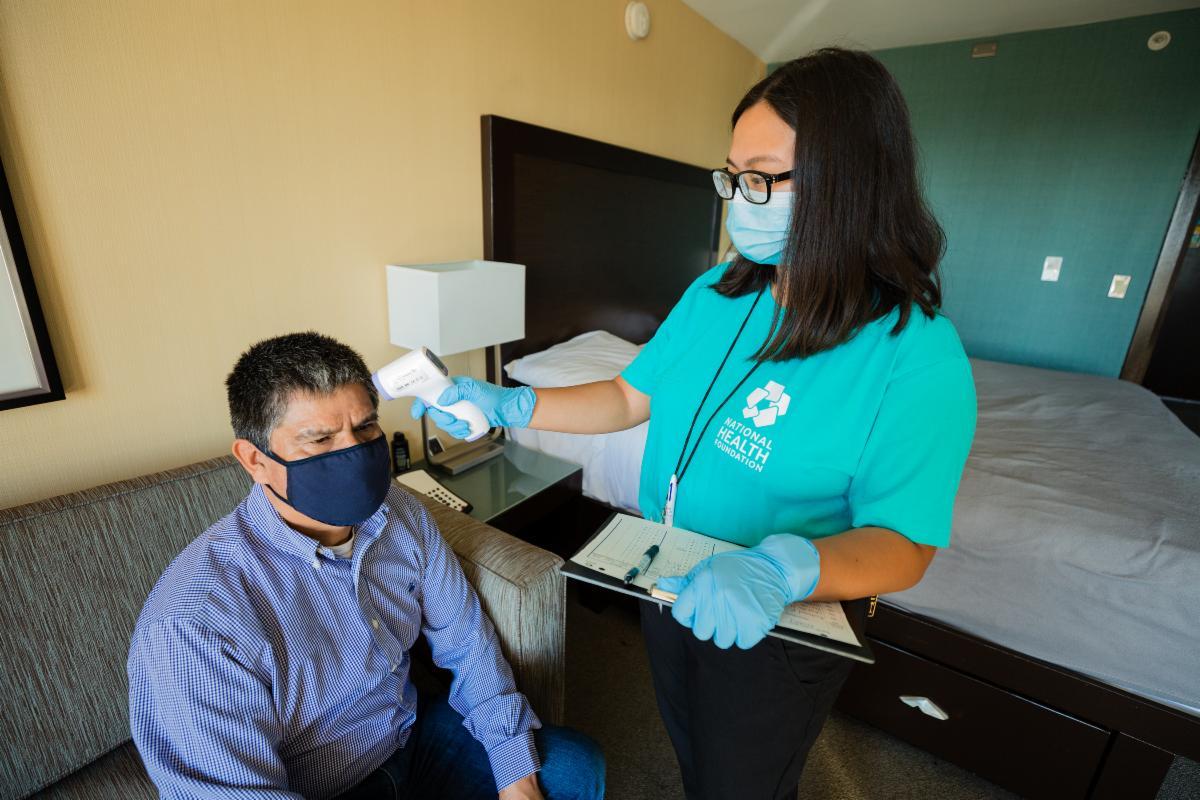 NHF staff member taking guest temperature.