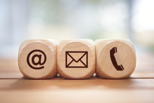 Contact us concept with wood block and symbols at_ e-mail address and phone