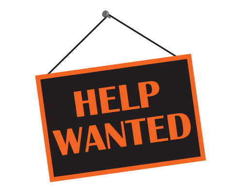 A black and orange help wanted sign with copy space