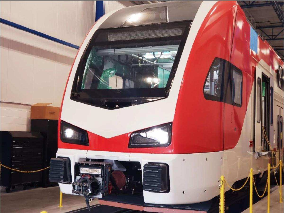 Caltrain in manufacturing with the headlights on.