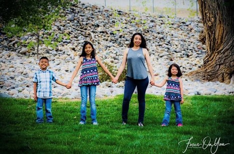 Christa standing, holding hands with her two daughters and son.