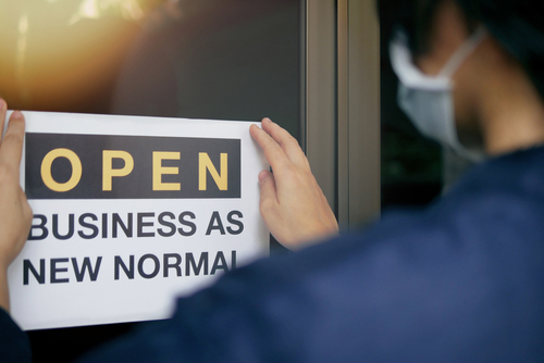 Reopening for business adapt to new normal in the novel Coronavirus COVID-19 pandemic. Rear view of business owner wearing medical mask placing open sign OPEN BUSINESS AS NEW NORMAL on front door.