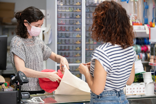 Horizontal view of woman buying clothes on a retail shop. Assistant at the counter wearing a protective face mask to avoid covid 19 contagious.