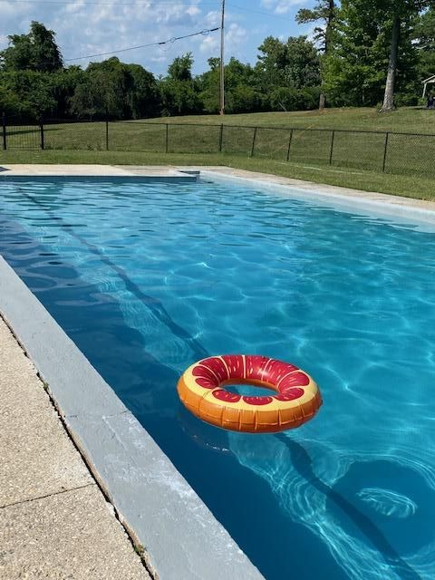 An orange swim tube floats a concrete pool filled with sparkling blue water