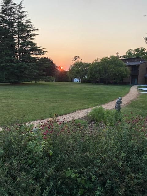 VCCA Felows Residence building with a flower garden in the foreground and sunset in the background