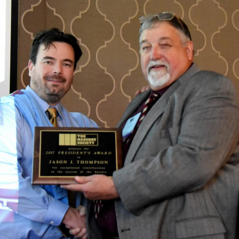 Jason Thompson (left) of the National Concrete Masonry Association receives the 2017 President's Award from Jerry Painter