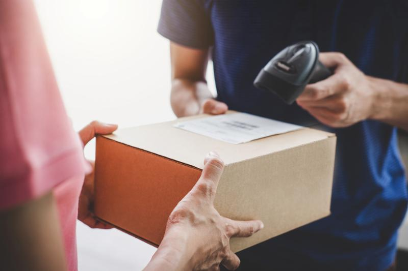 Home delivery service and working service mind_ Woman customer hand receiving a cardboard boxes parcel from service courier and deliveryman scan barcode to confirm delivery.