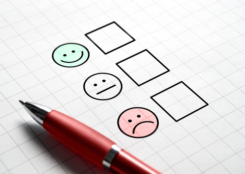 Customer satisfaction survey and questionnaire concept. Giving feedback with multiple choice form. Pen_ paper and emotion smiley face icons.