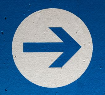 Directional arrow on a blue wall pointing left.