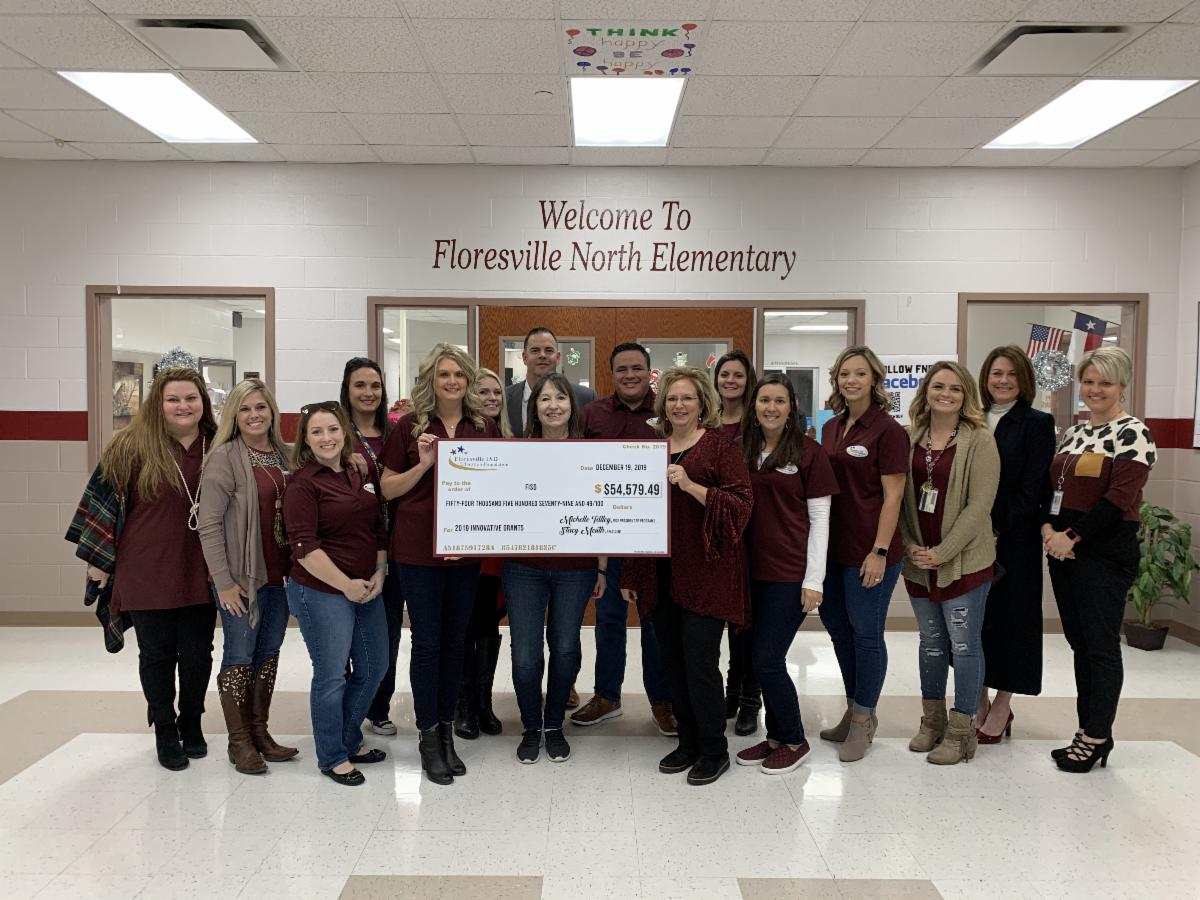 Education Foundation Members holding a large check