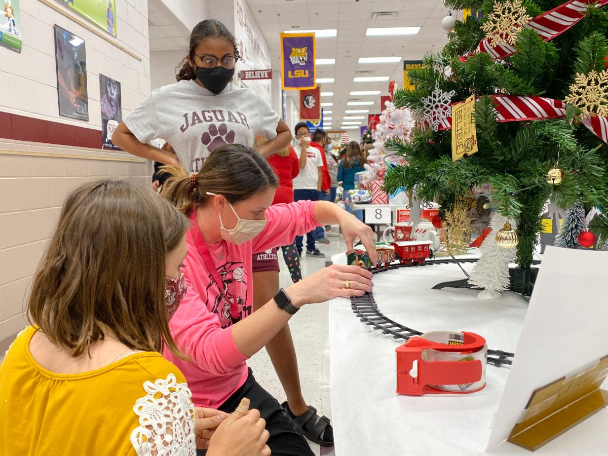 teacher and students decorating a Christmas tree with a train around the bottom