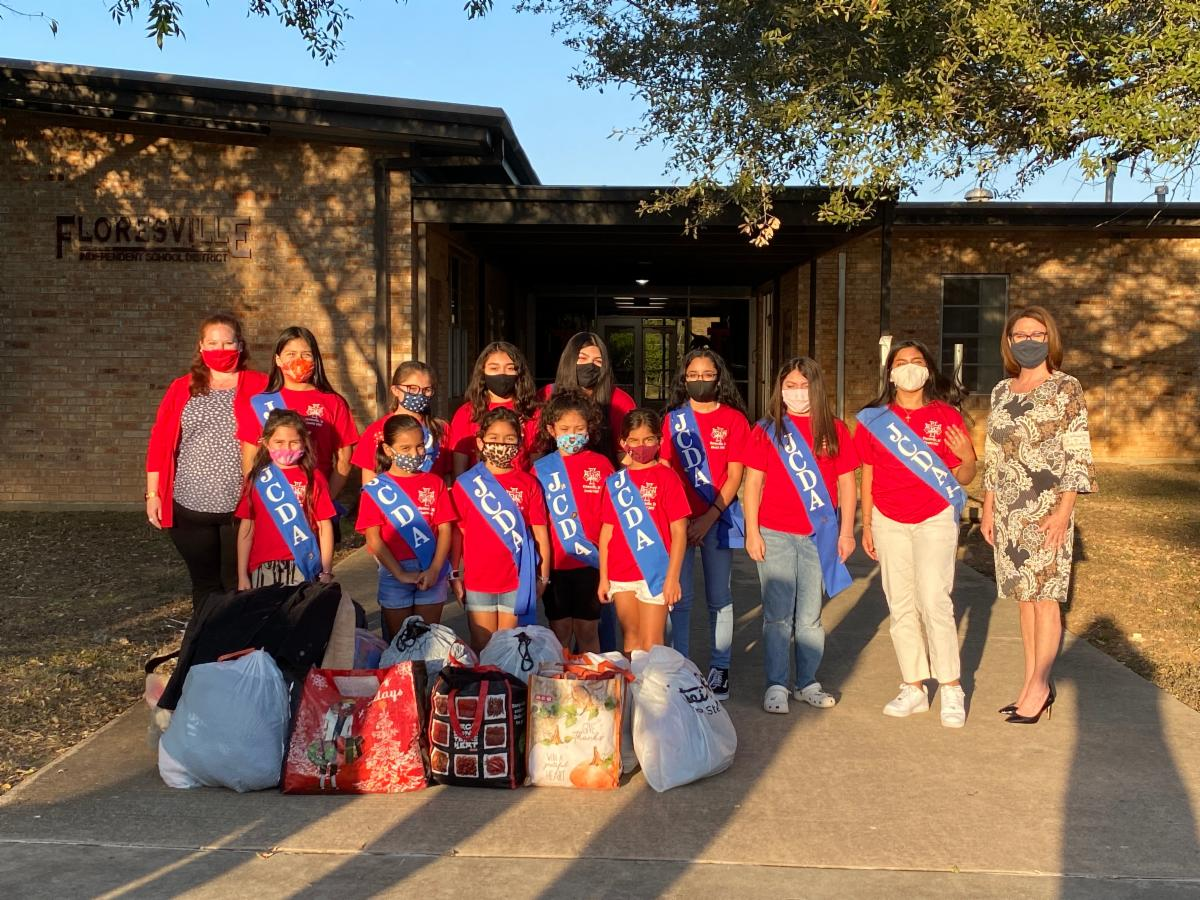 Junior Catholic Daughters holding jackets to be donated