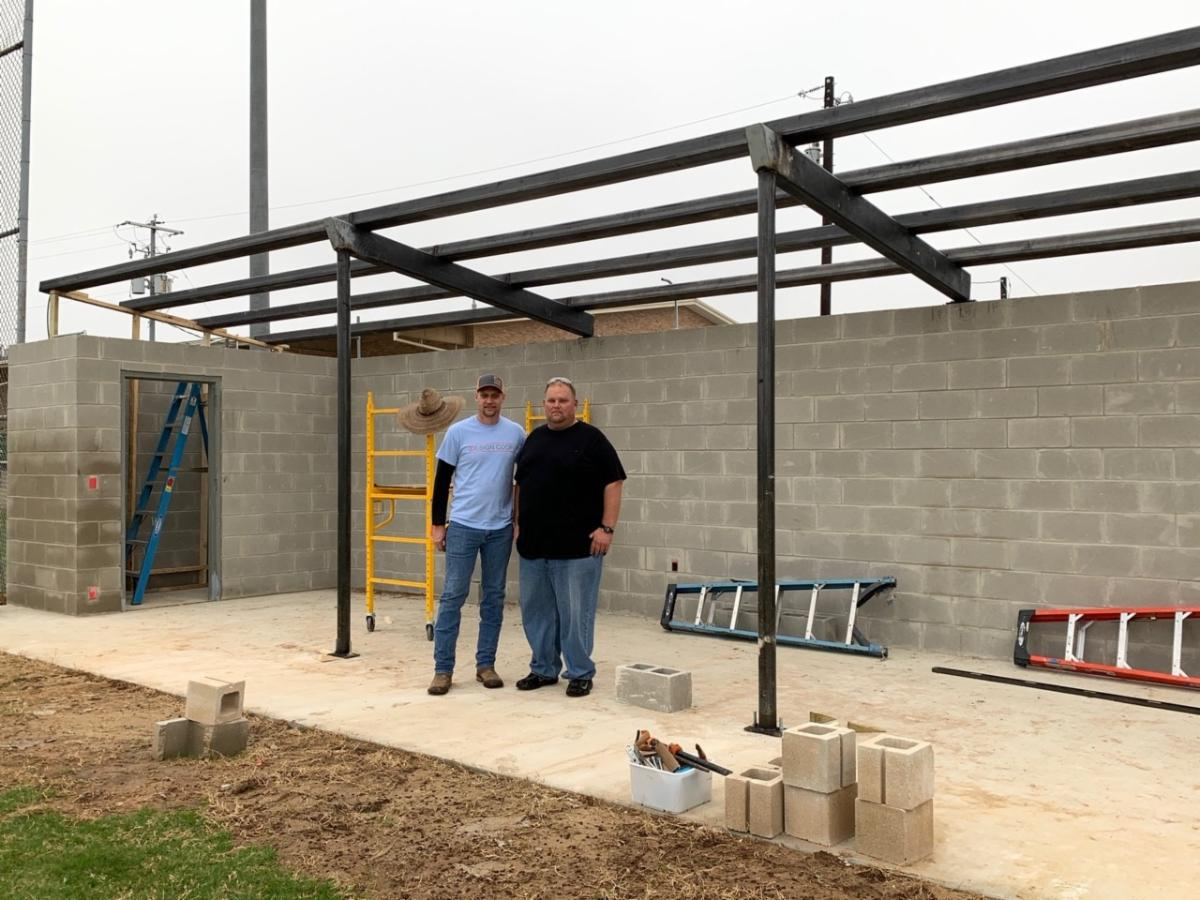 Two men standing in partially built dugout