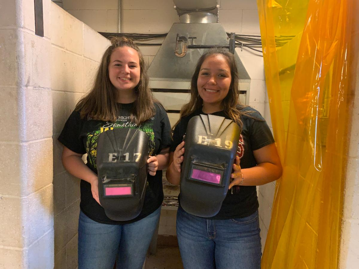 Two girls with welding helmets