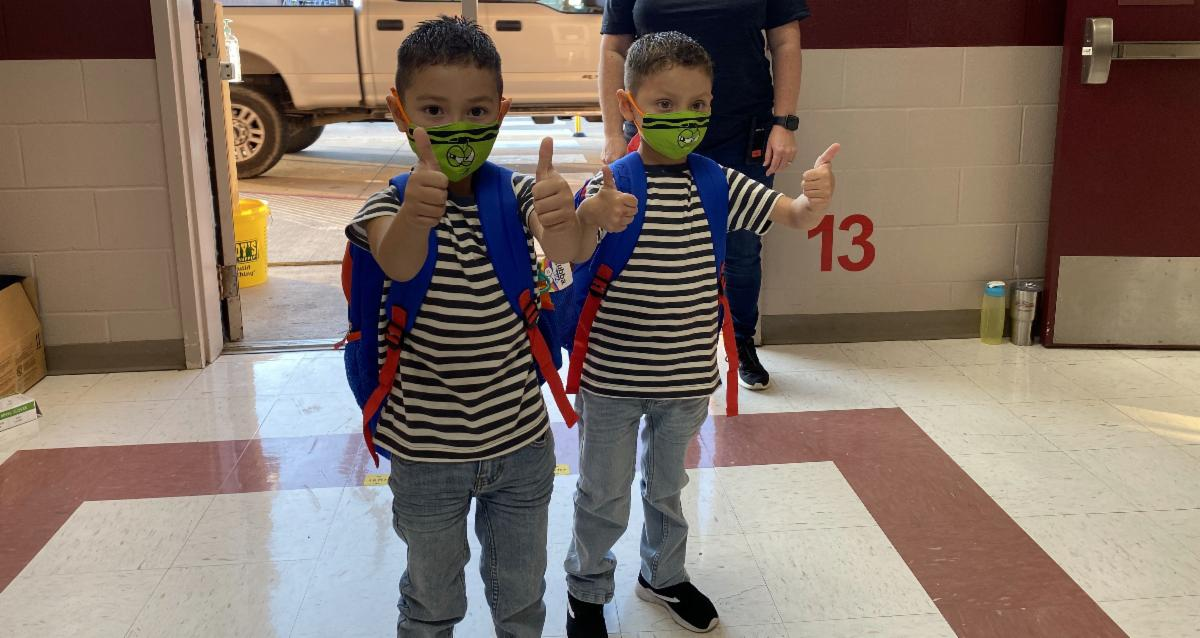 two little boys giving a thumbs up with masks on