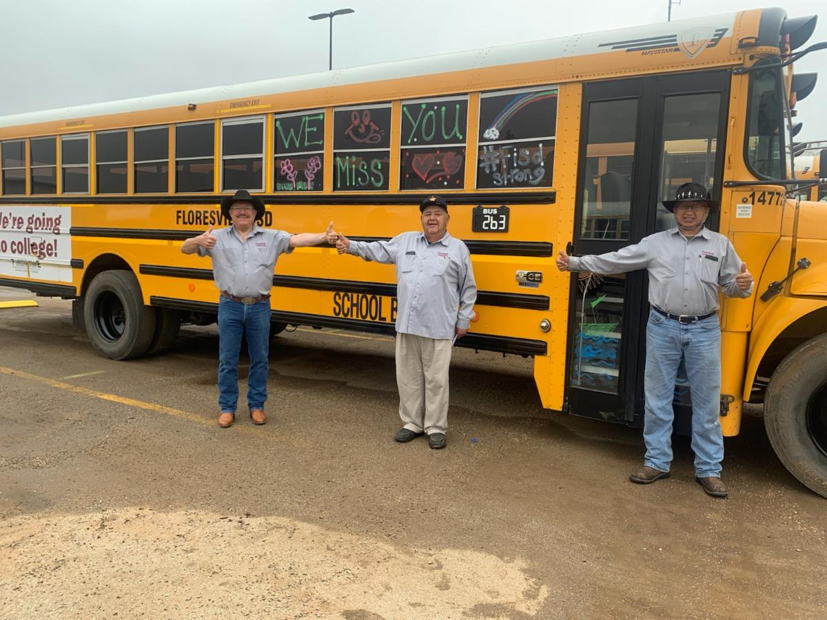 Three bus drivers in front of school buses