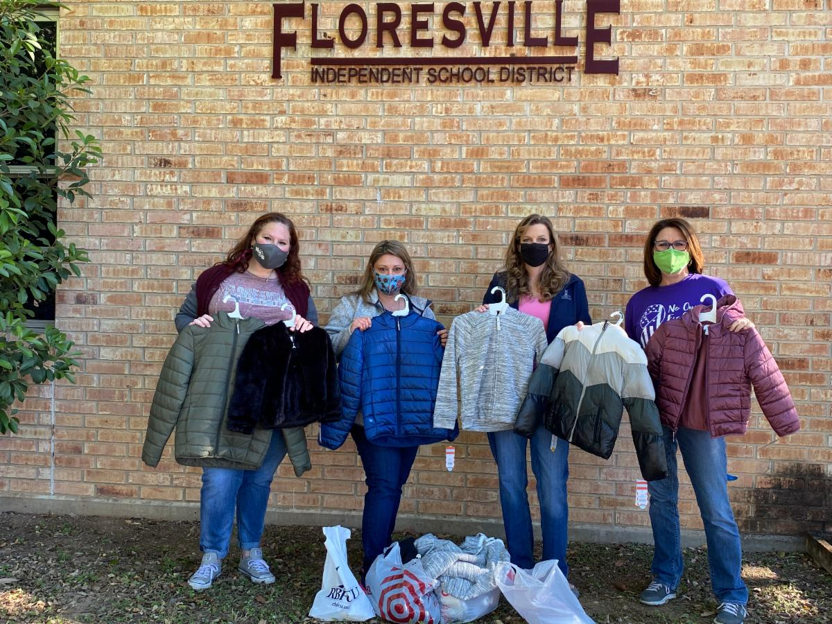 Group holding jackets to be donated