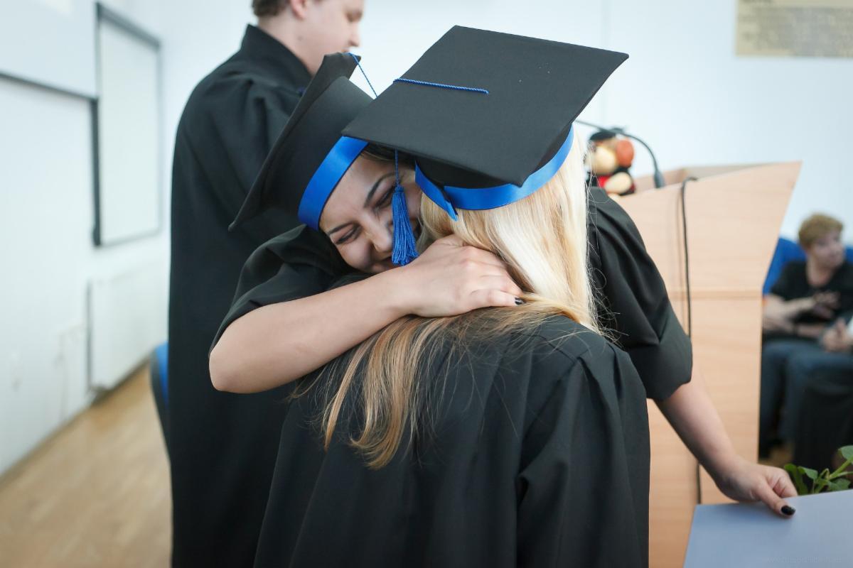 Two girls hug after receiving diplomas