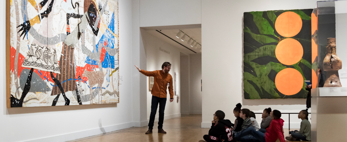 In the contemporary art collection, a gallery teacher explains a piece to students on a school field trip.