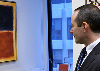 A masculine-presenting person in a suit looking at a Rothko painting that may be a forgery.
