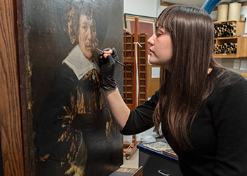 """Conservator Becca Goodman doing work on the painting """"Portrait of a Man"""" by Jan Hals with a paintbrush."""