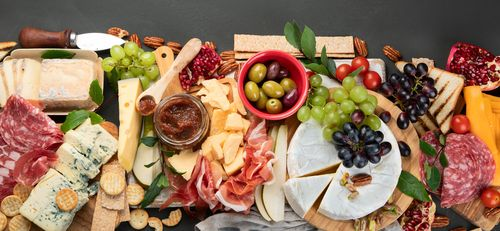Appetizers table. Cheese_ fuits and meat board on dark  background. Top view with copy space