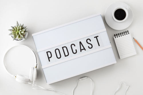 Podcast word on lightbox with headphones on white table_ flat lay