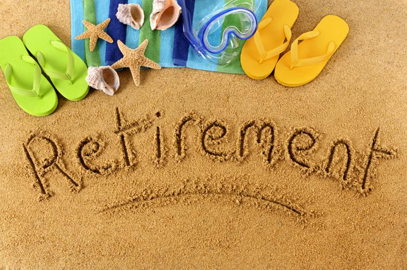 The word Retirement written on a sandy beach with scuba mask beach towel starfish and flip flops.